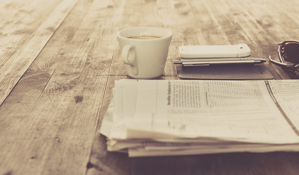 Coffee cup and smart phone on wooden table next to news papers
