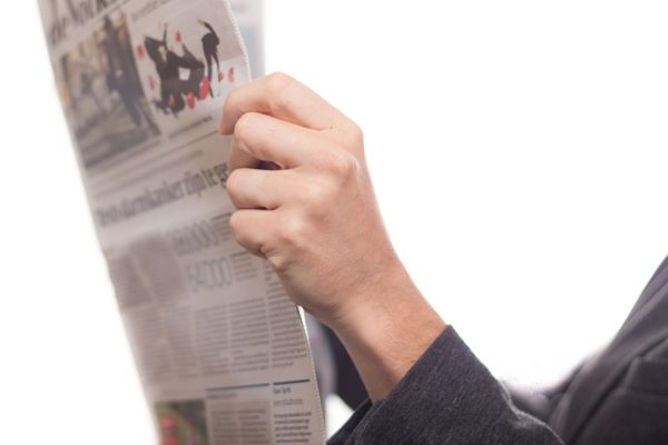 Person Holding Newspaper and Reading