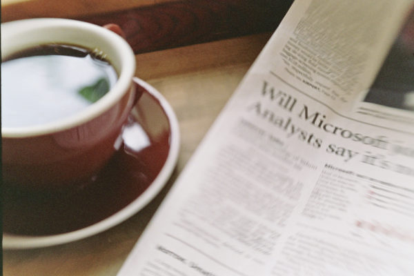 Newspaper with blurred coffee mug on the left