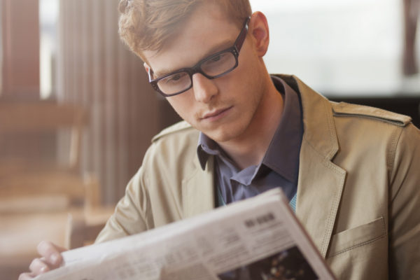 Man sitting in a restaurant and reading a newspaper
