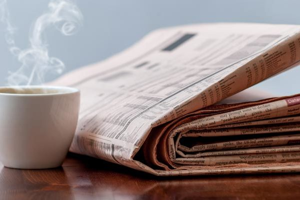 Newspaper and hot coffee mug